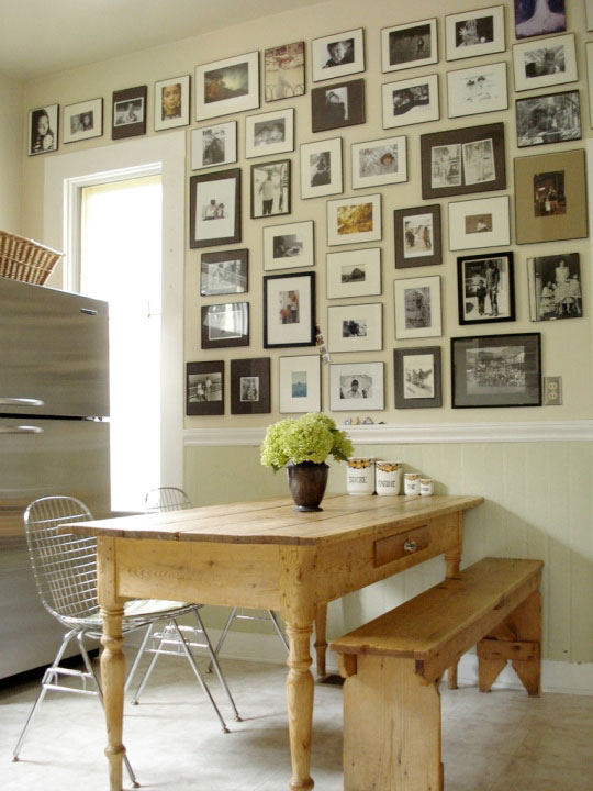 A very large collection of framed photographs that cover a whole wall.