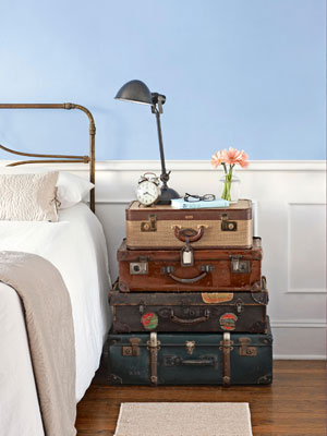 Vintage luggage and trunks used as a bedside table.