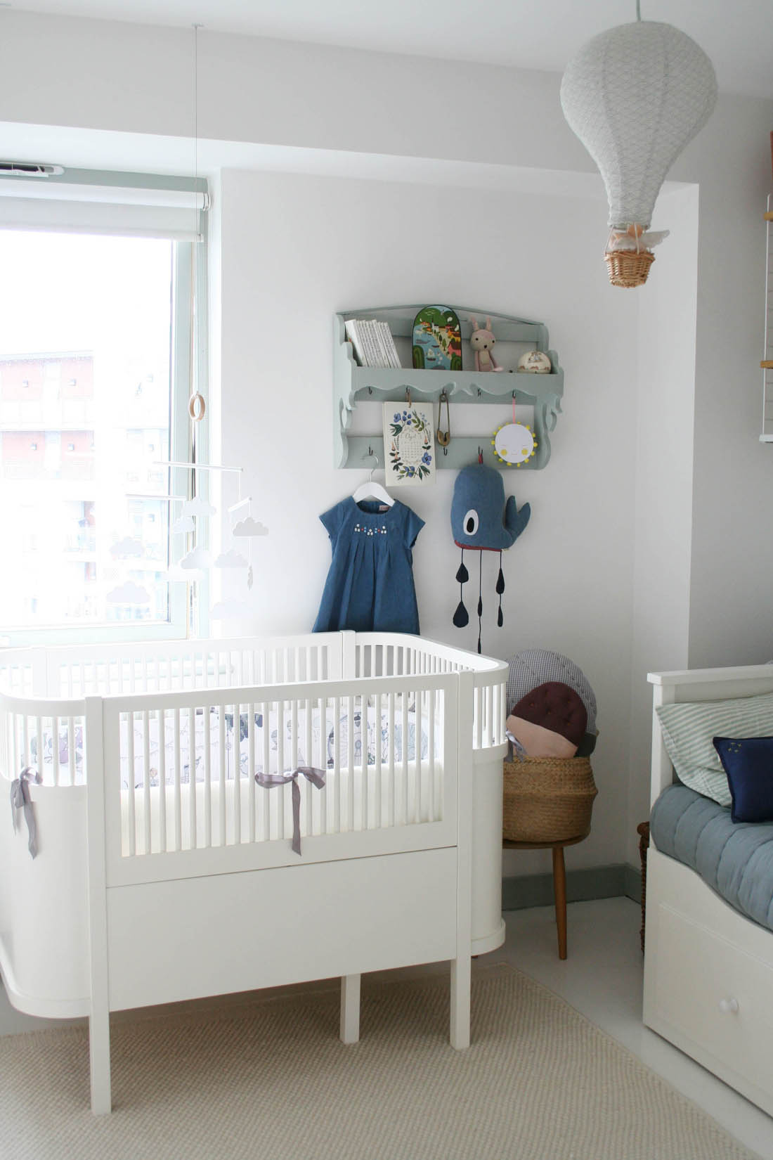 Gender neutral scandal style nursery decor inspiration with Sebra Kili cot bed with Garbo and Friends crib bumper and vintage shelf