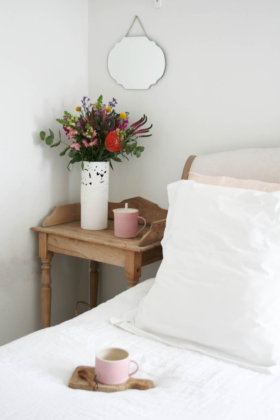 Minimal white bedroom with accents of dusky pink and vintage bedside table