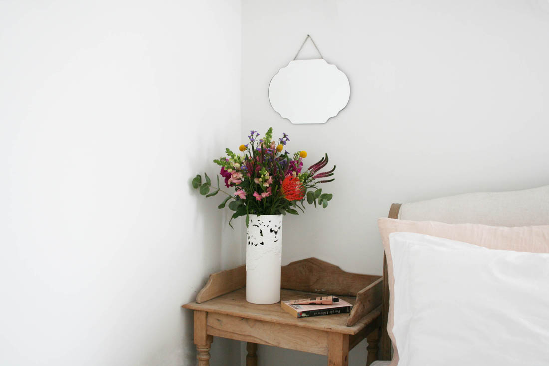 Minimal white bedroom with accents of dusky pink and vintage bedside table and mirror